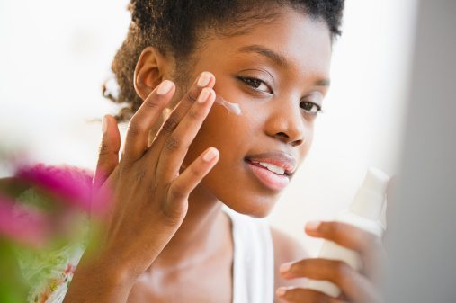 Black woman putting on face lotion