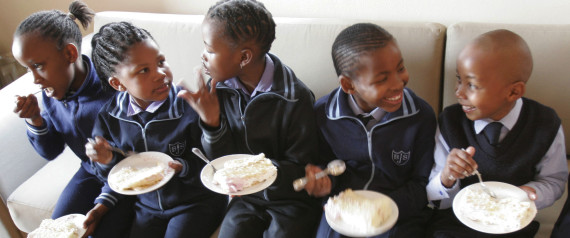 Children at the Bertrams Junior School eat birthday cake as they celebrate their school's 90th anniversary as well as Nelson Mandela's 90th birthday at the Nelson Mandela Foundation in Johannesburg Friday July 18, 2008. Mandela celebrated his 90th birthday Friday by urging the wealthy to share with the less fortunate and by saying he wished he had been able to spend more time with his family during the anti-apartheid struggle. Mandela was imprisoned for nearly three decades for his fight against apartheid.(AP Photo/Denis Farrell)