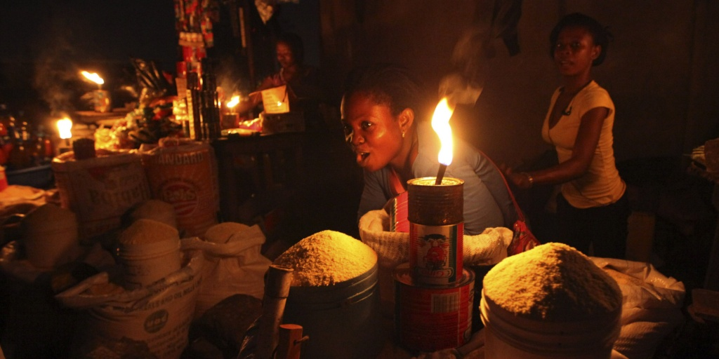 In this Tuesday, Aug. 24, 2010 photo, Esther Jacob sells cassava flour by lantern light in Lagos, Nigeria. Nigeria's president announced a multi-billion-dollar plan Thursday to repair and privatize the oil-rich nation's decrepit national power grid that forces people to rely on private generators to provide electricity. (AP Photo/Sunday Alamba)